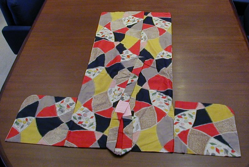abstract patches of yellow, gray, red, and black outlined with black line; a few patches of black and white and yellow patterns