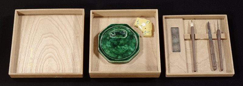 wooden calligraphy box with two stems of bright blue flowers with green leaves and gold veins; includes brush, silver weight or brush rest, wooden tool rest, two metal and wood tools, green ceramic ink stone, and yellow ceramic water dripper