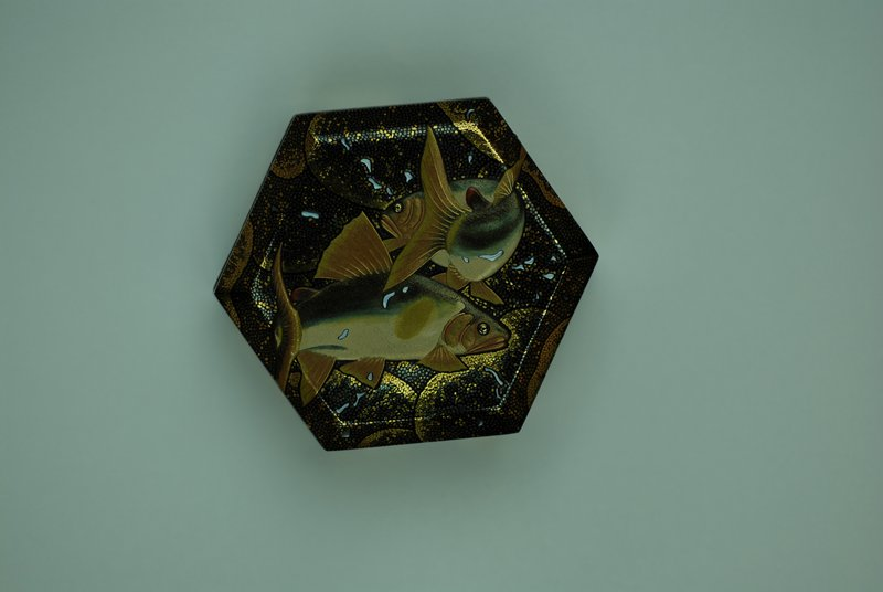 hexagonal box with two swimming trout on lid; bubble motif in tiny gold flecks; other gold flecks in background