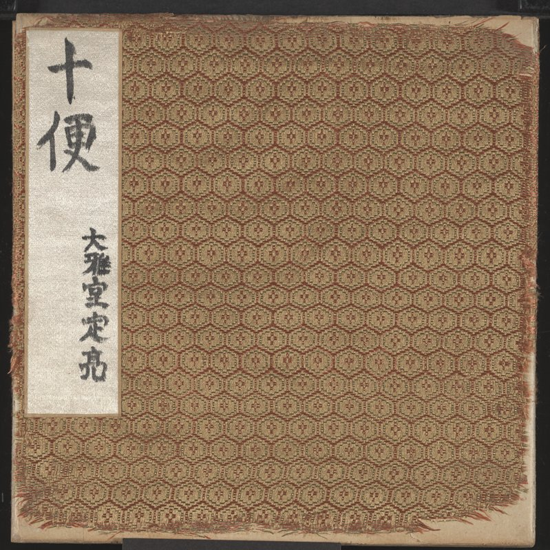two gold and red fabric covered albums enclosed in tri-folding blue case; albums contain circular vignettes of landscapes
