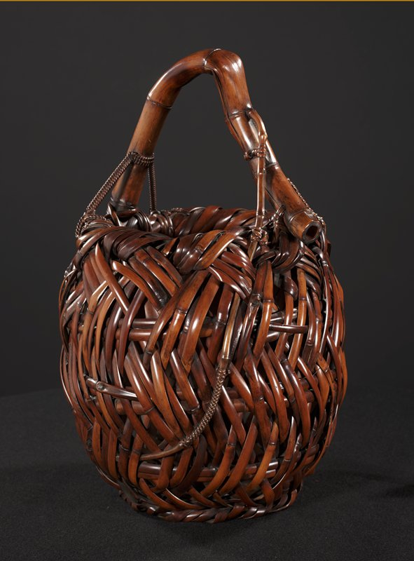 woven oval form basket with raised bamboo handle with crook in it; a few thin braided strands placed irregularly; inset container: bamboo cylinder lined with copper with fluted sides that sits inside basket to hold flowers
