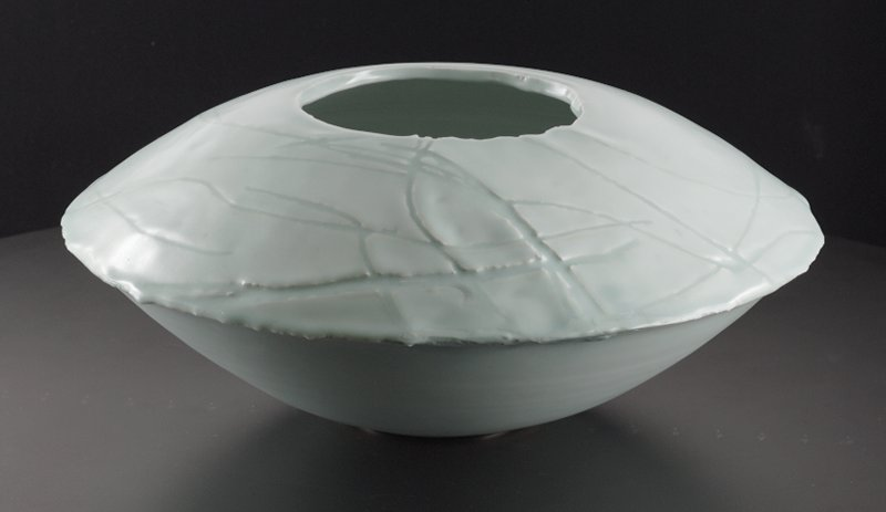 "low, round, ""flying saucer"" shaped object with irregular, narrow mouth; crisscrossing incised lines on top; thin metal base"