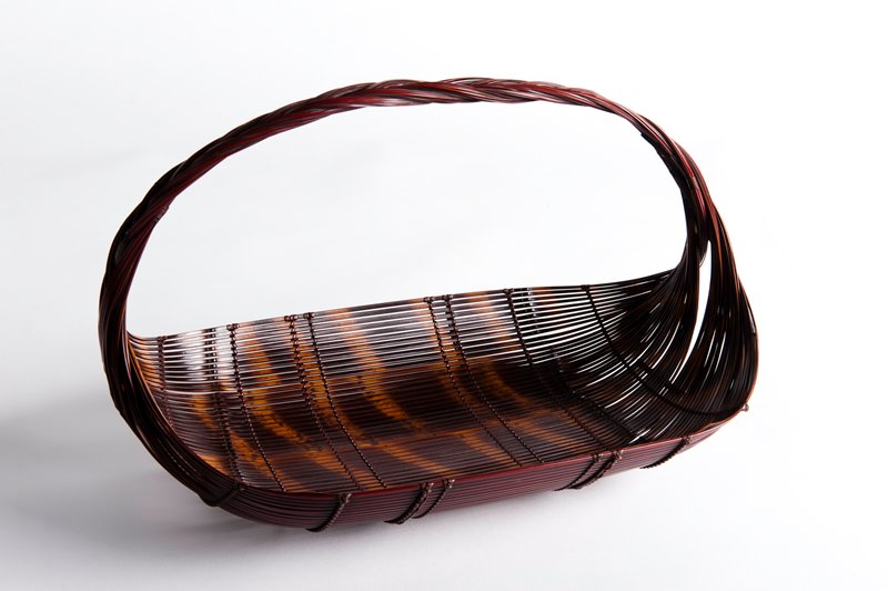 oblong, low basket with upward curving edges; open, horizontal weave; strands sweep upward into continuous, braided handle; spotted dark pattern in basket; reddish handle