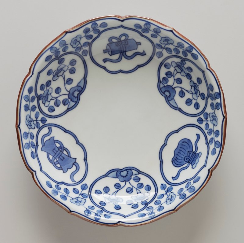round plate with gently scalloped edges; arabesque vignettes featuring alternating floral patterns and items like scrolls, pouch, etc.; brown lip; blue rings around bottom foot