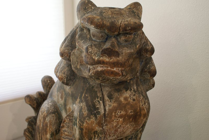 seated lion with large, furrowed brow; barring teeth; erect, fanned tail; remnants of pigment throughout