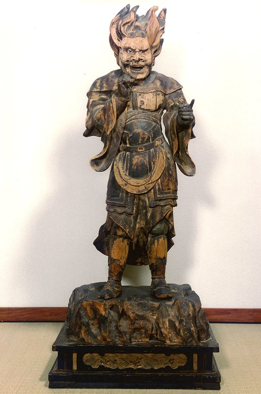standing wooden figure with flame like hair, and fierce expression wearing warrior clothing; wide stance with PR hand clenched in fist toward chest; PL hand clenched in fist with index finger pointing outward; base with carved and painted waves