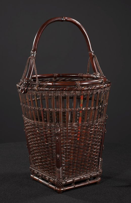 woven basket with square bottom and circular top, predominately brown finish with some vertical elements painted red and gold, or black and gold; handle is a single piece of curved bamboo; smaller, braided arches intersect each handle a few inches above end
