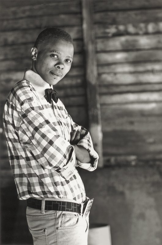 standing young person from waist up with PL side to camera, on L side of image; s/he has arms crossed on chest and is wearing plaid shirt; white wood frame with museum glass