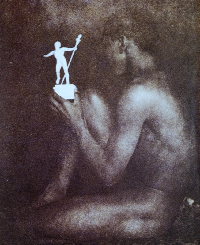 nude male in profile, with a bent R knee, sits on leopard print cloth and holds a small statue of classical male figure in his L hand