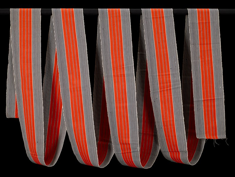long strip of woven fabric; black and white stripes flanking four central orange stripes with thin black and white stripes between