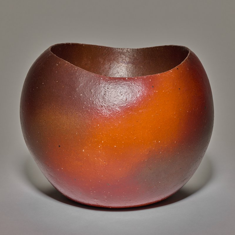 low, bulbous bowl with shallow interior; rim is higher on two sides; rust and red/orange in color