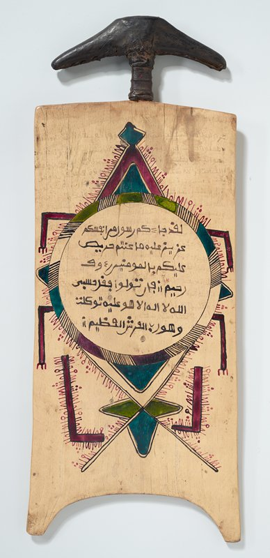 wooden board with leather-covered handle at top; one side decorated with design in red, green and black horizontal linear elements with text, diamonds, triangles and half-circles with hatched lines; opposite side decorated with circle with text and lines--abstracted animal?