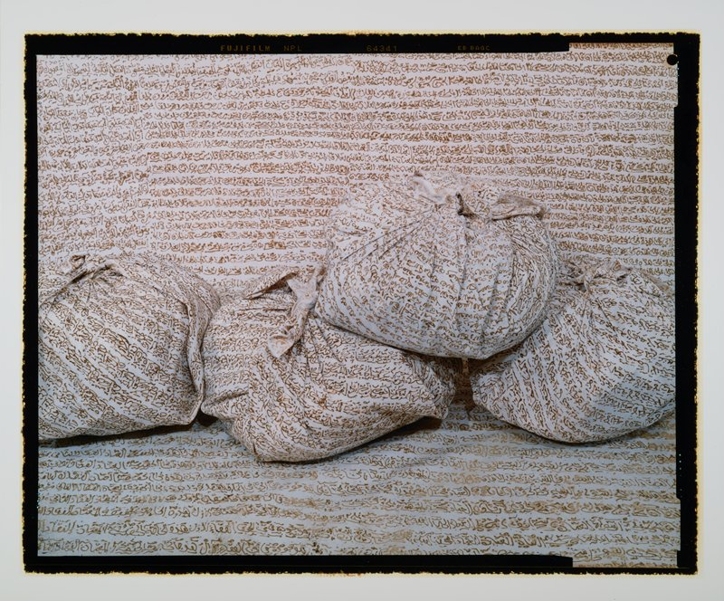 four cloth bundles on a white ground; bundles and ground have lines of brown text overall