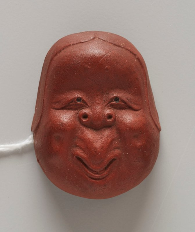 netsuke in the form of a mask; red clay; smiling face with round cheeks and long philtrum; nostrils on top sides of nose, like a dog; small droopy eyes; mouth in the form of a V; 2013.29.1217.1-6 received attached to patterned orange, cream and blue ribbon (ribbon in poor condition--shredded)