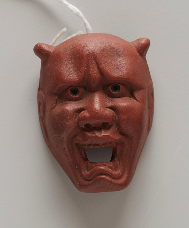 netsuke in the form of a mask; red clay; demon face with small horns; open mouth, with fangs; wide flat nose; beady eyes; large stylized ears