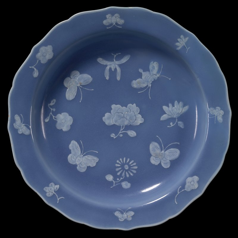 shallow bowl shape; ring foot; heavy base; sloping rim with scalloped edge; medium blue glaze with white flowers and butterflies, in very low relief