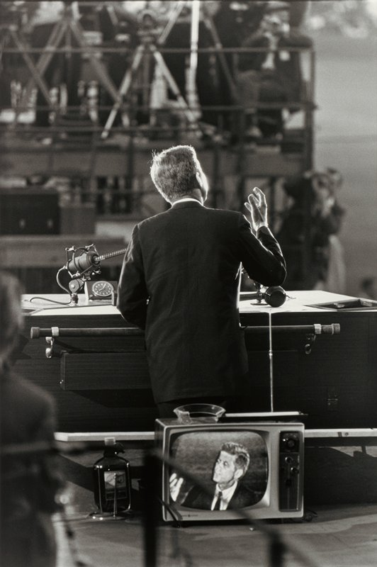John Kennedy's face on TV screen at front center; back of Kennedy's torso and head visible behind TV, giving a speech, gesturing with his PR hand; figures on scaffolding (?) in background
