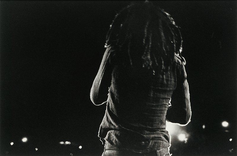 torso and head of figure, seen from back, with long hair in many braids, wearing a long-sleeved shirt; dark ground with spots of light at bottom of image