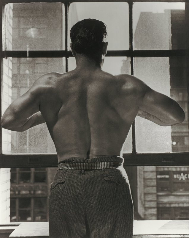 torso and head of shirtless man seen from back wearing tweed trousers with patterned belt, holding his arms up with elbows bent; man looks out window at city buildings