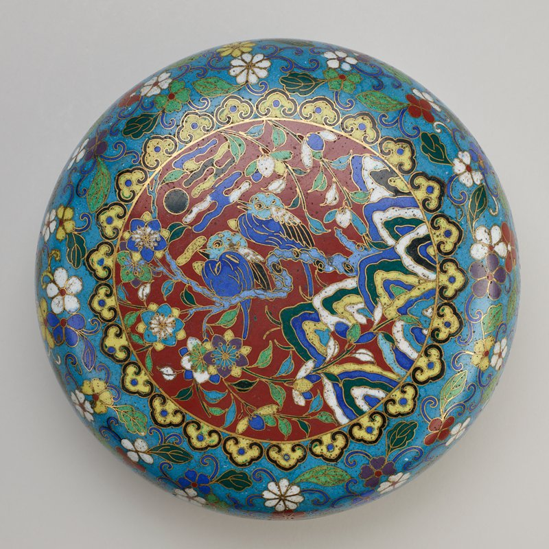 lozenge-shaped box on raised foot; blue ground and interior; scrolling multi-colored flowers; central round medallion with pair of blue birds on a branch against a maroon ground