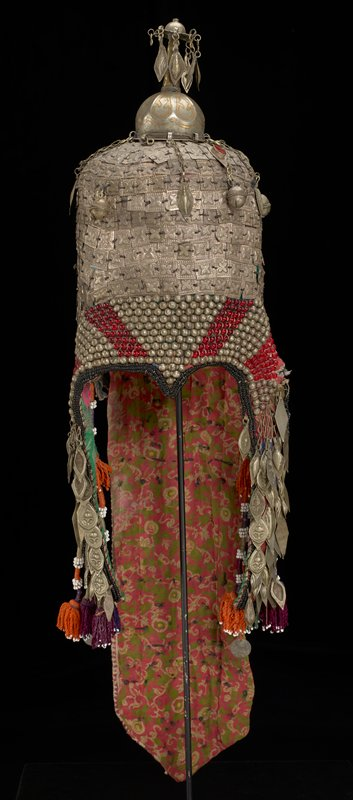 tall cap covered overall with hammered silver squares with quatrefoil designs; elaborate finial with teardrop-shaped drops and gilt elements; long embroidered fabric tail on back with dark pink ground and white, pink and black floral and geometric design, covered overall with flat hammered pendant drops and stamped metal discs with primarily floral designs; backing of back tail is printed pink cotton with green, white and yellow scrolling floral design; row of multicolored tassels topped with beads at top of back; vertical fabric element on each side have printed fabric on front and back (pink ground with floral print on front--green and pink brocade on back) with primarily diamond shaped drops overall; twisted tassel on each side of hat with white beads and purple, green and orange threads; silver metal and red beads on front bottom
