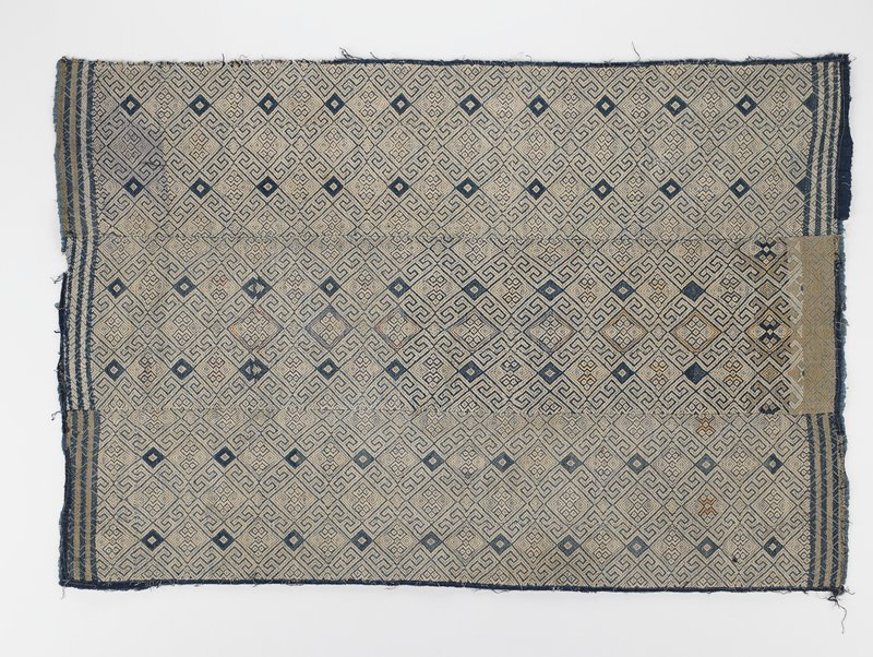 three woven panels sewn together; tan and blue geometric pattern including blue diamonds throughout and tan and pink diamonds in central panel