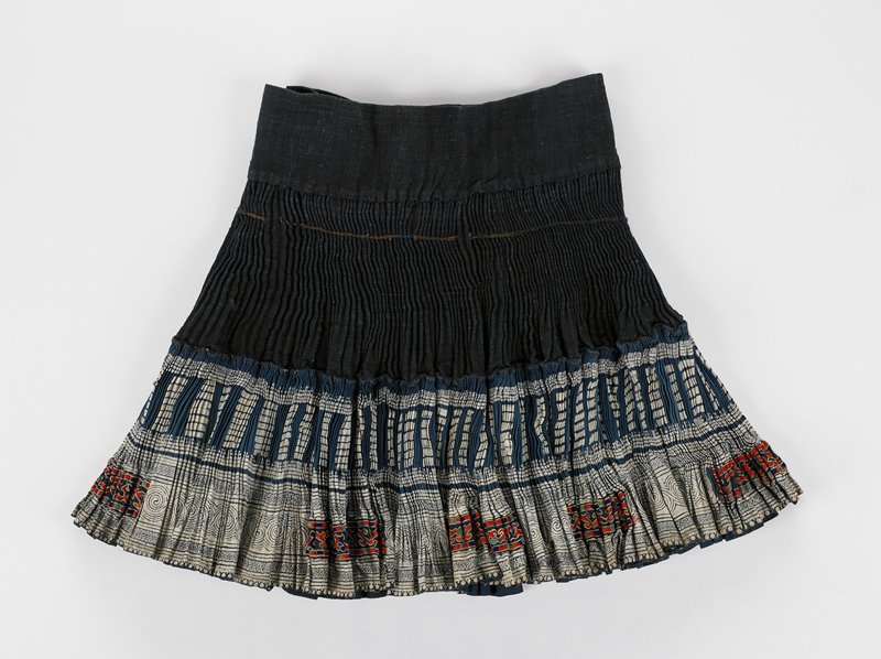 accordian skirt; lower half decorated by two bands of batik; six rectangular applied embroidery interspursed in lowed band