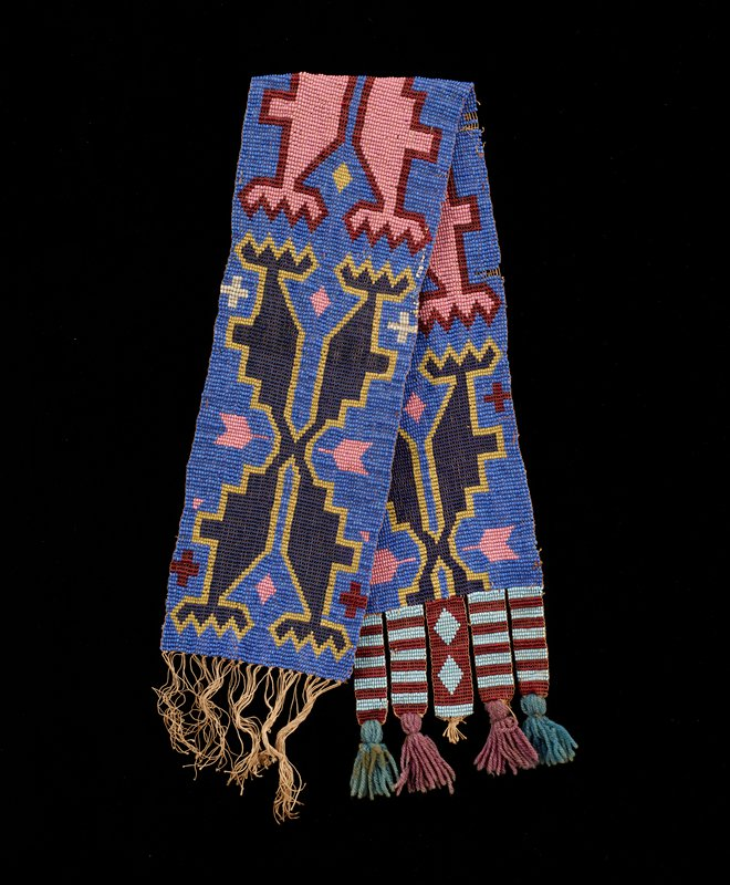 "beaded panel with beaded strips/tabs terminating in pairs of turquoise or light purple wool yarn tassels forming fringe; four tabs have light blue and red stripes, central tab has red ground with two light blue diamonds; body has medium blue beads on ground, with symmetrical X-like forms with steps and zigzags in predominately pink, dark blue, red and yellow beads, with pink ""X"" at center, one dark blue ""X"" at top and one partial dark blue ""X"" at bottom"