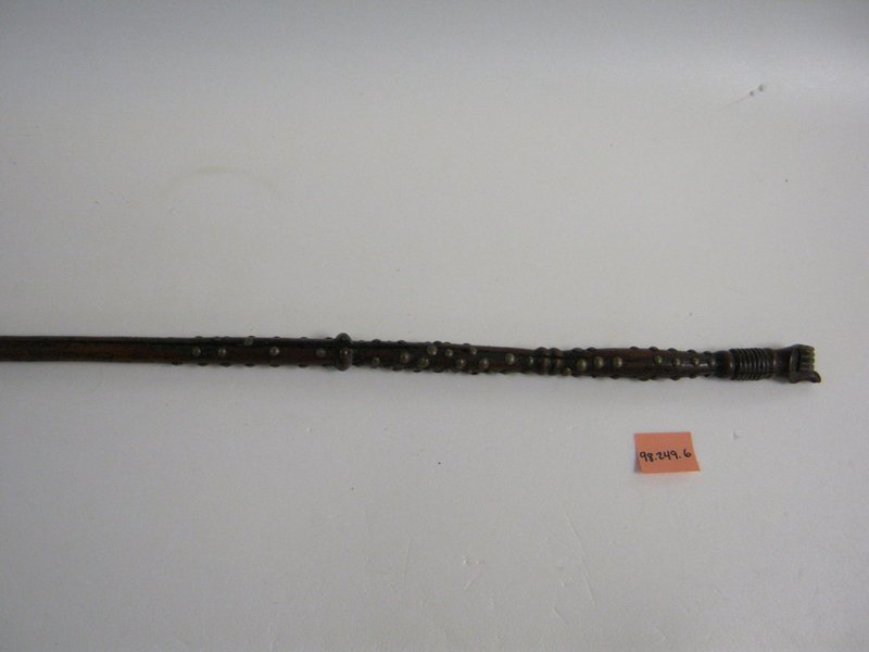 Staff with hand on top; top half covered with brass studs with black metal mount