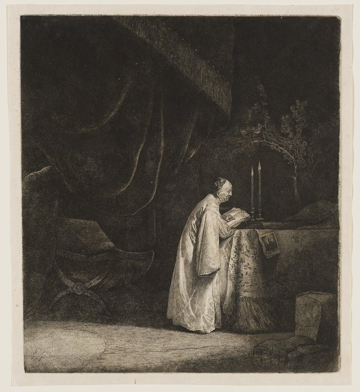profile of a priest illuminated by two candles; writing in a book, leaning on cloth covered desk; trees, and large, draping curtains in background