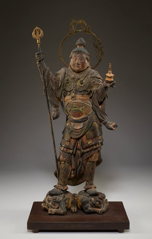 demonic figure standing on two subdued, grimacing demons, one of whom is looking up with bloodshot eyes; figure is standing with wide stance, PR arm raised to hold separate staff, PL hand open, with hole to hold separate golden spindle; demons mount onto base, and tabs on figure's feet insert into demons; separate halo with golden flames mounts to back