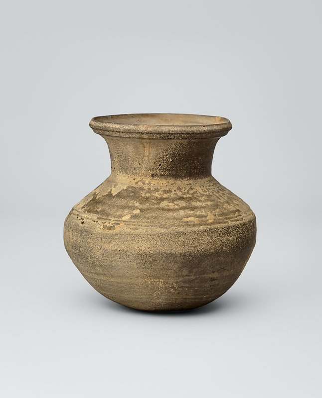 jar with three incised lines around widest part; high neck, slightly flaring mouth with incised lines around outside; remnants of tan ash glaze