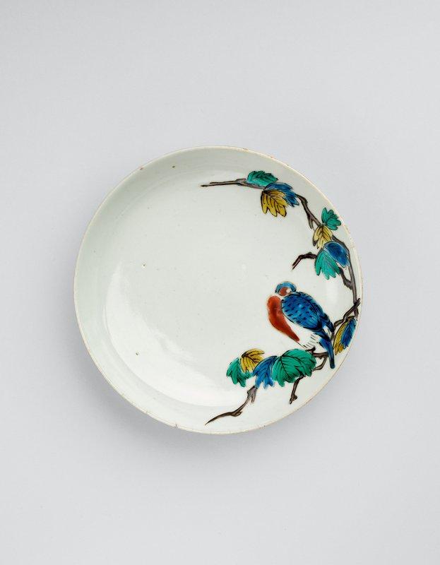 small white plate with blue and red bird perched on a branch at R; blue, green, and yellow leaves on branch, curving down R side