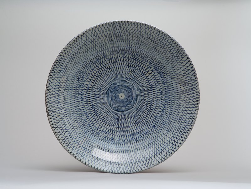 large round porcelain platter with underglaze blue fishnet design; spot at center; design continues outside