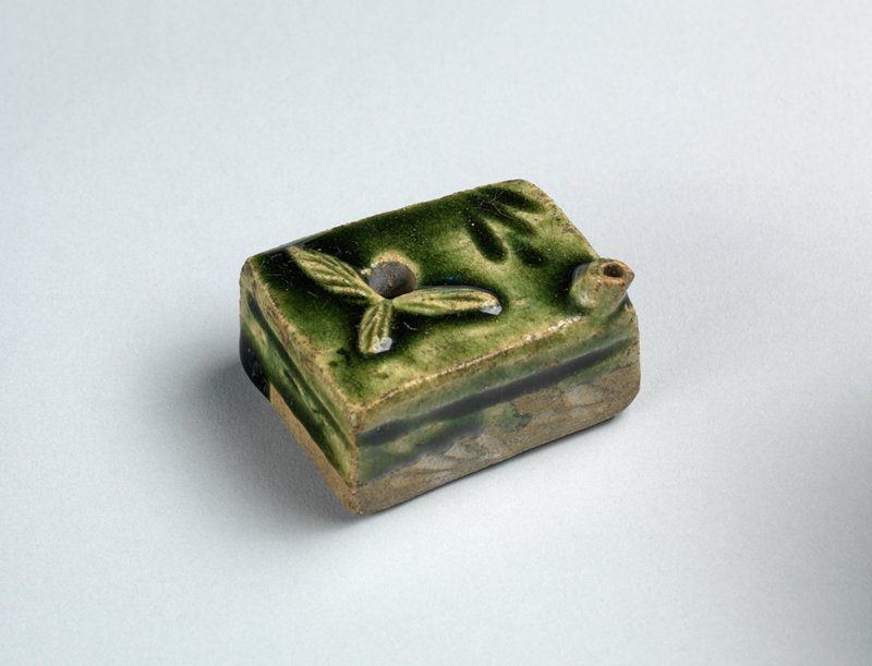 irregularly shaped rectangular clay box; green glaze; three raised leafs around hole on top; incised lines on sides; areas of pooling green glaze