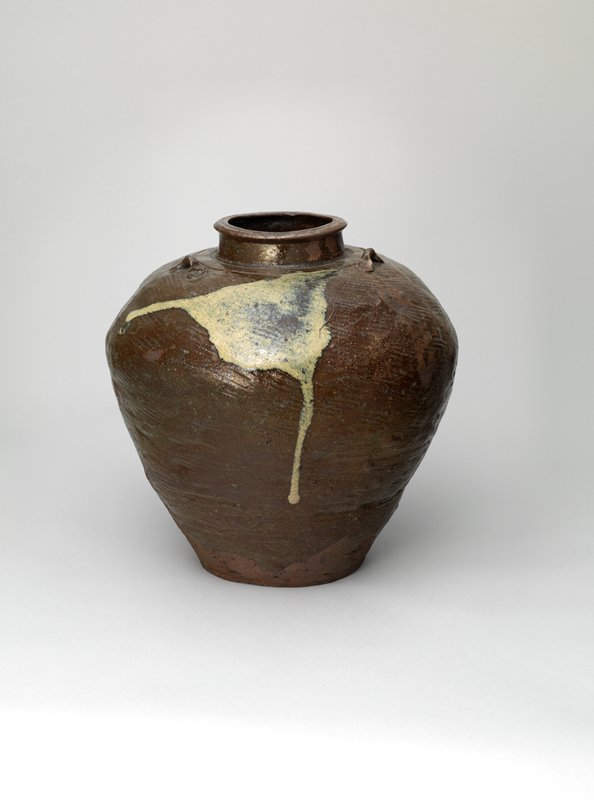 brown-glazed jar with narrow base, wider shoulder; short, erect neck with larger lip; incised lines around base of neck; incised lines around lip; three small bow-like handles; patch of white slip on shoulder that drips to the side and down