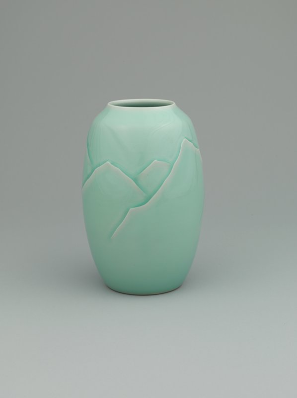celadon glazed vase with low relief motif of abstracted mountains; narrow foot; low, narrow mouth with subtly raised lip