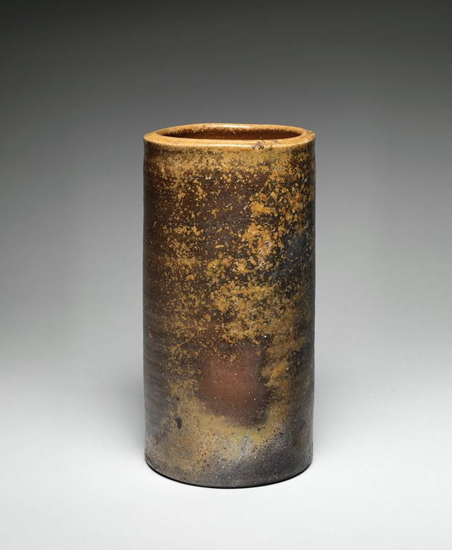 cylindrical vase with natural ash glaze primarily on the front and lip; inner surface curls in slightly at the top; groove-like depression along edge of mouth; clay has feldspar pieces in it; gray color in lower front from the flame