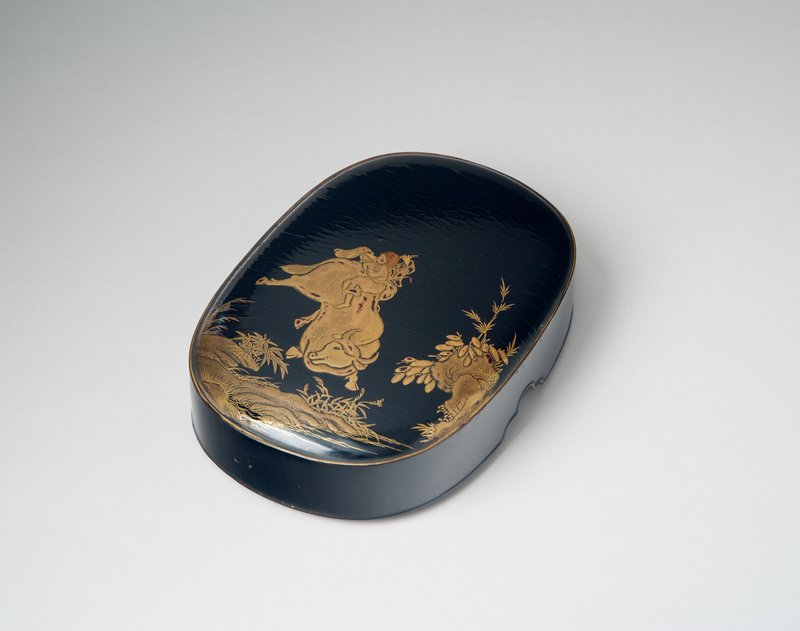oval black lacquer container; design in gold of boy playing flute, riding on back of a water buffalo who is kicking his heels into the air; low rocks with bamboo and grasses at bottom and R