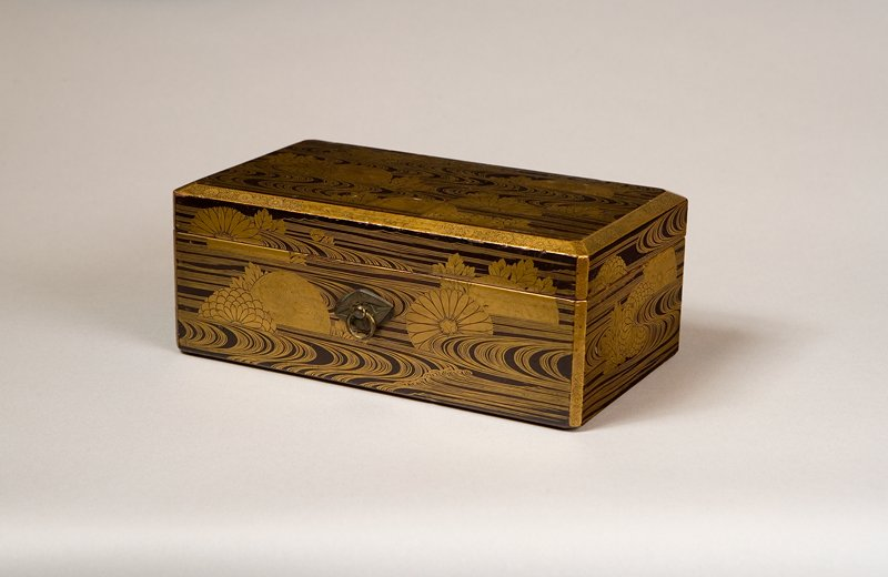 oblong box with beveled corners; lid with beveled edges; chrysanthemums and leaves amid stylized waves motif; beveled edges are decorated with chrysanthemums and vines on gold ground; crane-shaped metal fittings for cords on front and back of box