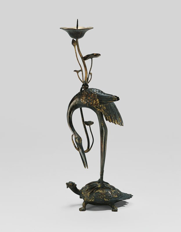 crane standing on tortoise with fringed tail; crane's neck bent down, holding frond of lotus in its mouth; stem extends upward with two flat leaves, a small bud, and open blossom with spike for candle