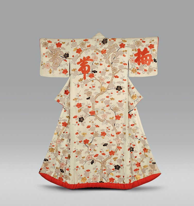 kimono with cream ground and red-orange lining, with padded hem; decorated with net-like flowers in brown; black ink outlines of scrolling stems, buds and flowers; some solid black flowers with metallic gold details; orange silk embroidered flowers and buds; some gold detailing on stems and on some flowers; some green embroidered stems; large bold characters on each sleeve and chest at upper PR and on upper body on back