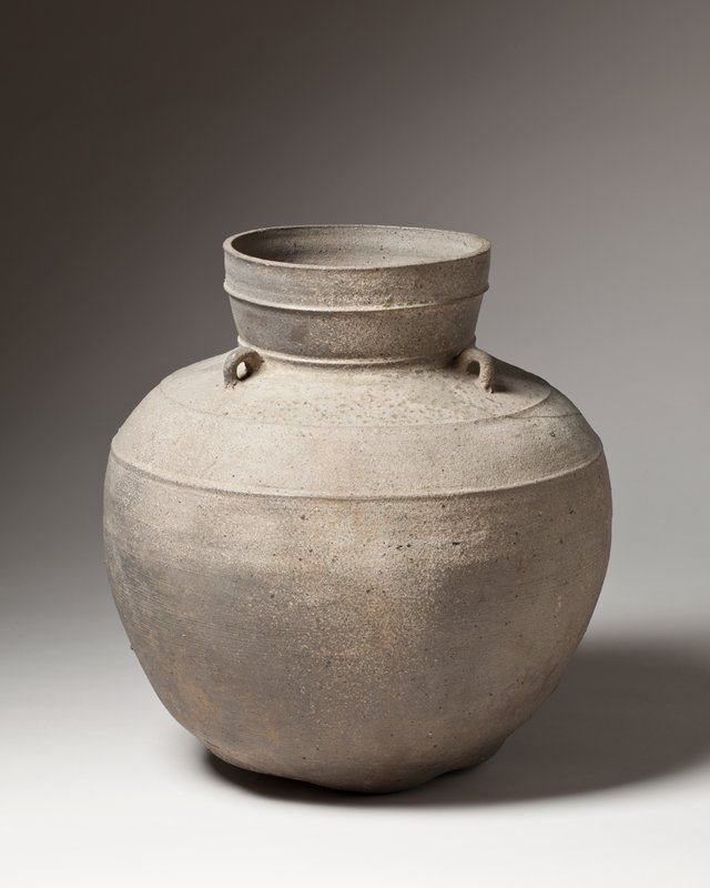 jar with high, slightly outward flaring neck; four small clay loops affixed to shoulder, near joint of neck; four raised rings around shoulder and neck; lumpy lower portion of body; overall grayish in color with flecks of light greenish glaze