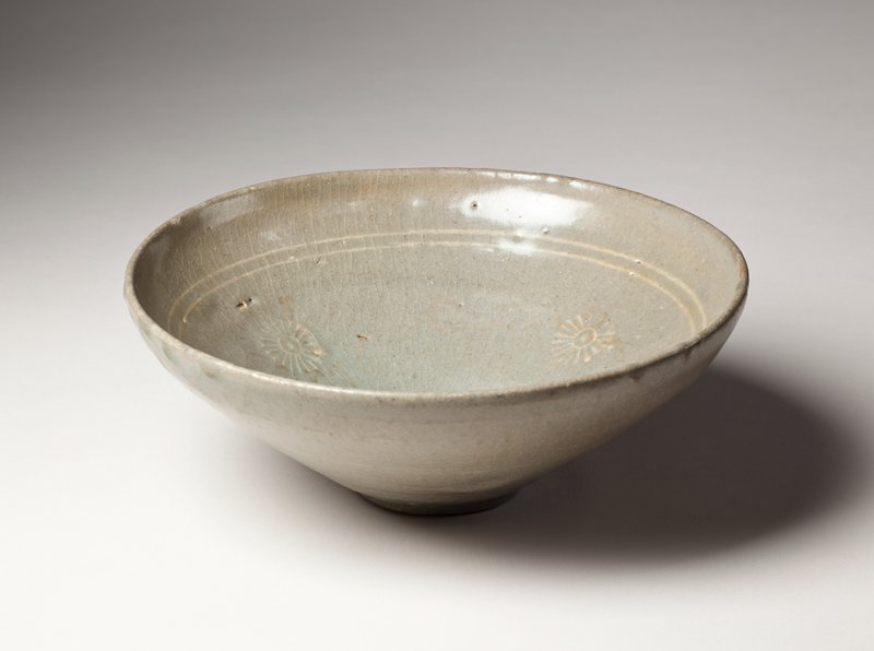 bowl with narrow base; three stylized chrysanthemum emblems inside under two white rings near lip