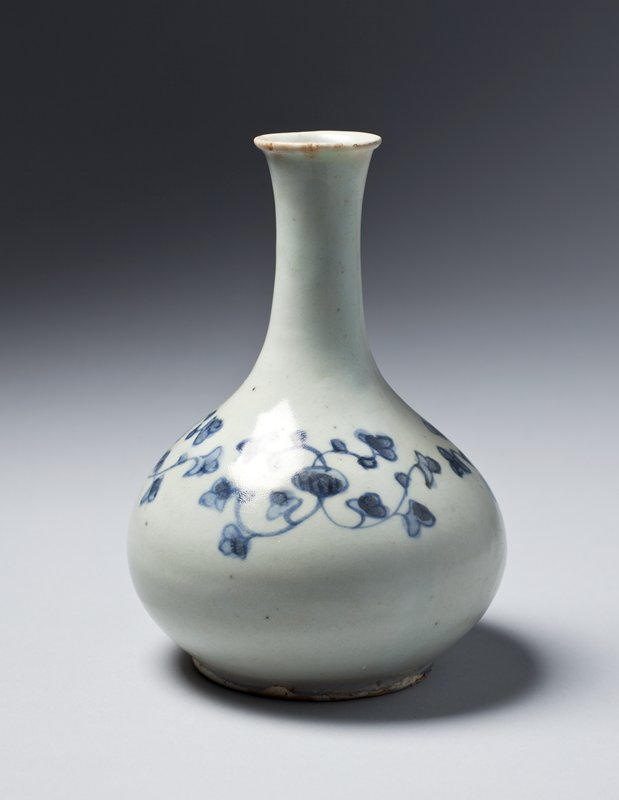 small white bottle with blue underglaze designs of small flowers on vines; long neck, slightly flared mouth