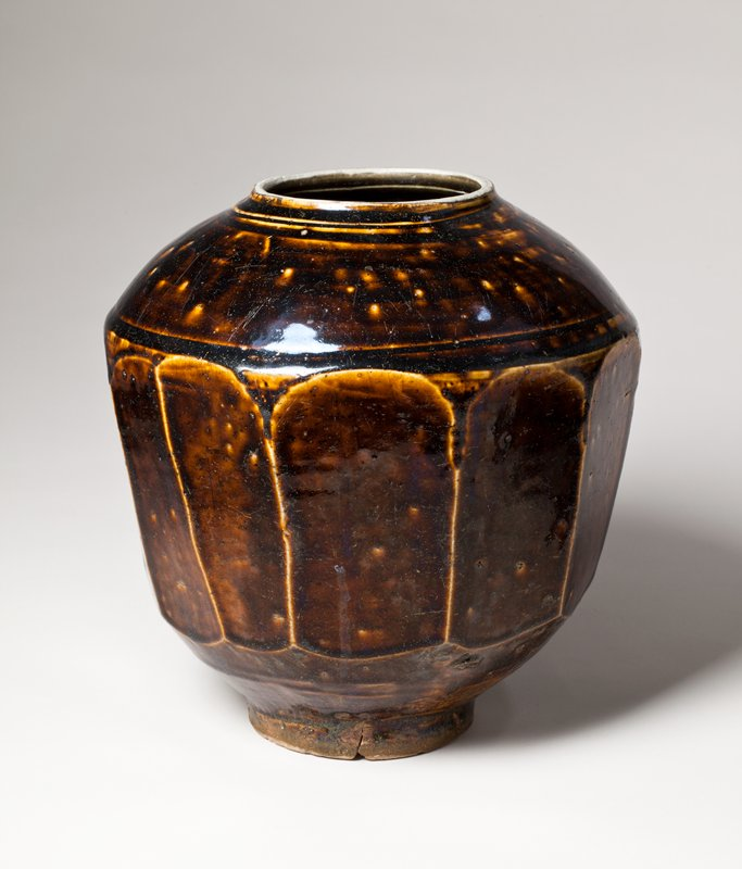 lopsided jar with very dark brown glaze; faceted walls, rounded shoulder, low, flat mouth, small foot; incised lines around lip and shoulder; lighter material shows through in raised areas below glaze; no glaze on mouth