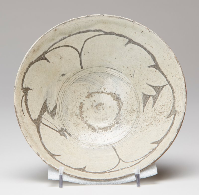 shallow bowl decorated with brushed white slip; incised abstracted leaf design inscribed and highlighted with darker gray glaze
