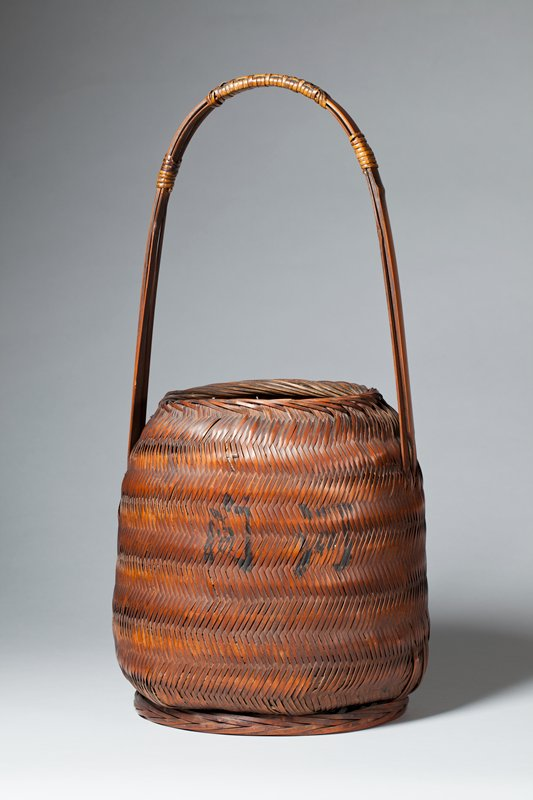 bucket-shaped basket with erect, rounded handle; closed, chevron weave; two Japanese characters on one side; block of text with border opposite side