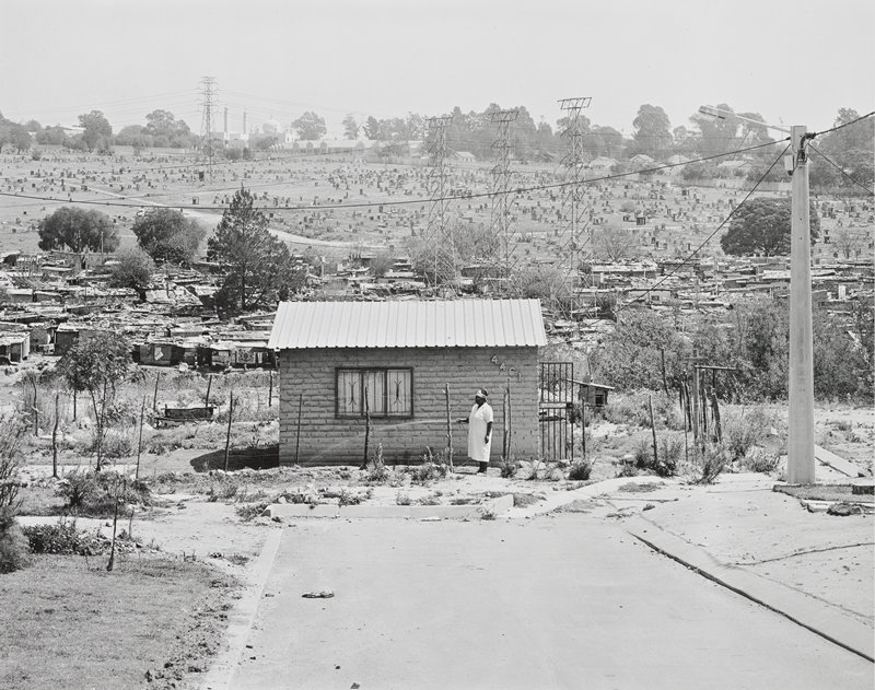 black and white photograph of a woman with watering with a garden hose in front of a tiny rectangular brick house; in the background are many power lines, a cemetery and shacks