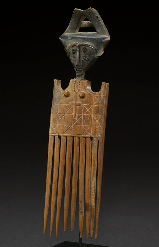 "comb carved to have head of woman wearing a headdress, which meets at point with top scooped away; there is a hollow space in the middle; head is upside down triangle; nose and eyebrows are connected, forming a palm-tree-like shape; eyes are lopsided circles that are divided in two; mouth is simple indentation; left cheek has a series of dots that form square, the right cheek has a slanted pointed ellipse; ears are flat and stick out from the side of the head; neck is long and thin with rings carved into it and a rosary hanging from it; from the neck down is the comb; top is square, with small scoops taken out of each side; figure has small, raised breasts; flat square is sectioned into a square grid pattern; every other square has an ""X"" through it; square separates at the bottom into the thick teeth of the comb; head is a dark, black wood, while the bottom is a light honey-colored wood"